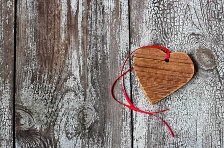 Wooden heart with red ribbon on a wooden table photo