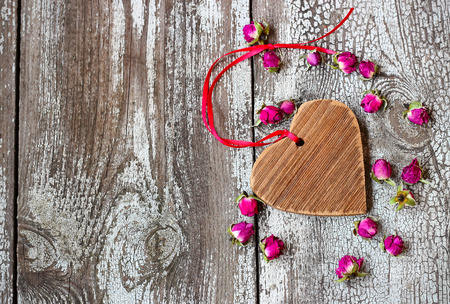 Wooden heart with red ribbon with small dried rosebuds on a wooden table photo