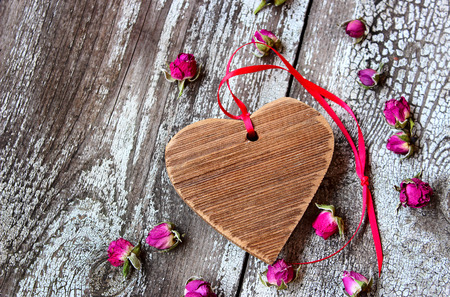 Wooden heart with red ribbon and small dried rosebuds on a wooden table photo