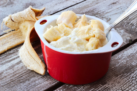 vanilla ice cream: ice cream with slices of banana in ceramic bowl