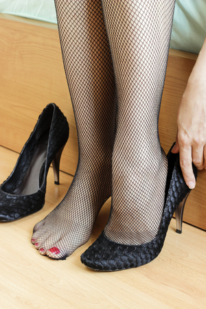 nackte schwarze frau: Womans Füße mit Netzstrumpfhose und Heels Lizenzfreie Bilder