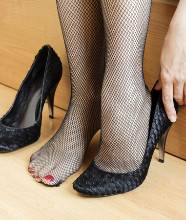 erotic women: Womans feet with fishnet tights and heels Stock Photo