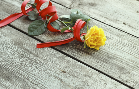 day valentine: Yellow rose with red ribbon on a wooden background Stock Photo