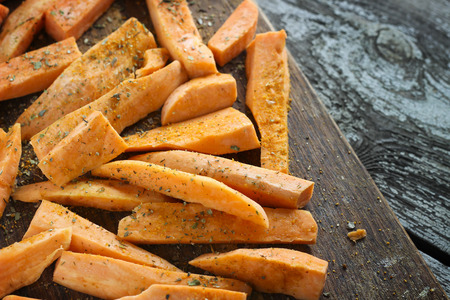 sweet potatoes: Fresh cut slices of sweet potatoes with oil and herb, made into fries, ready for cooking