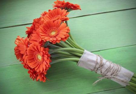 gerbera daisies: Bouquet of orange gerbera daisies, green plank background, holiday concept