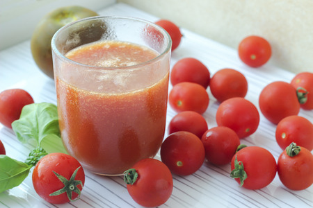 Glass of tomato juice and fresh tomatoes cherry on white background, selective focus