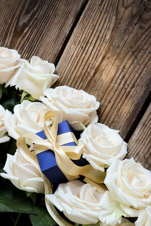 White roses and gift box over rustic wooden table, holiday background, selective focus