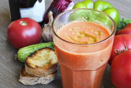 gazpacho: Summer cold tomato gazpacho soup in a glass and ingredients - tomato, cucumber, paprika, onion, garlic, bread, olive oil, wooden background