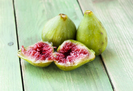 two and a half: Whole two green figs fruits and one fig sliced in half with red flesh, selective focus