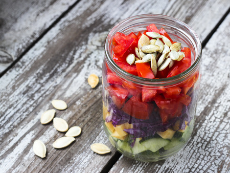 Cucumber, cheese, tomato, red cabbage and pumpkin seeds salad in a jar on rustic wooden table, selective focus