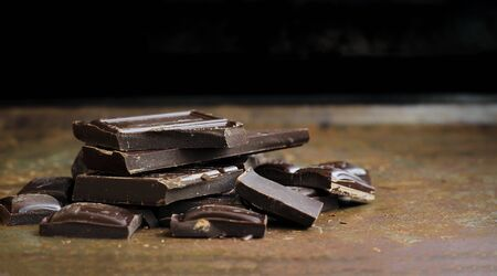 Chopped dark chocolate on a used grunge rusty baking tray Stock Photo