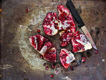 Fresh peeled pomegranate with seeds on old grunge background, toned, selective focus Stock Photo