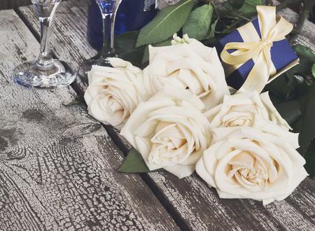 White roses, sparkling wine bottle, champagne glasses, gift box, festive table setting, selective focus, toned image