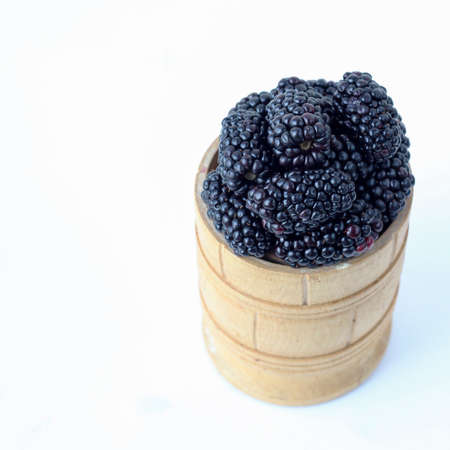 Blackberry in a wooden bowl on a white background, selective focus