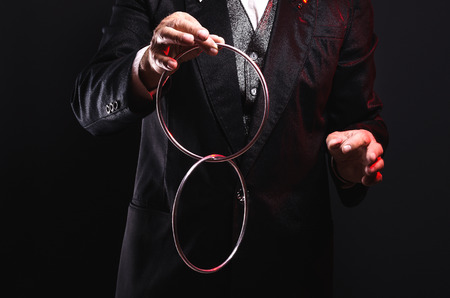 Magician shows trick with metal rings. Sleight of hand. Manipulation with props.