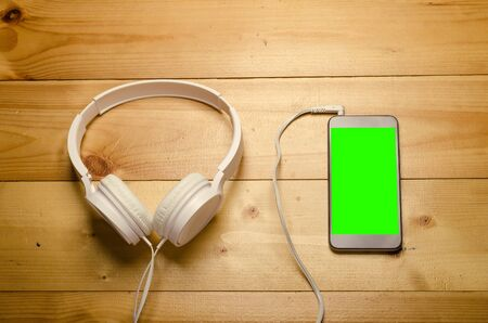 Modern headphone with cable and gadget with green screen. White headphones connected to phone on wooden table. Stok Fotoğraf