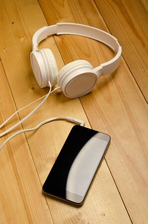 Modern headphone with cable and gadget. White headphones connected to phone on wooden table.
