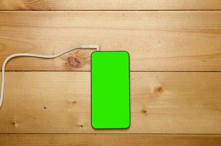 Modern gadget with green screen. Phone connected with cable on wooden table. Stok Fotoğraf