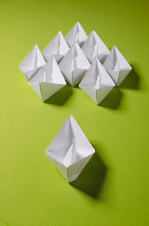 White origami on green background. Group of handmade ship. Stock fotó