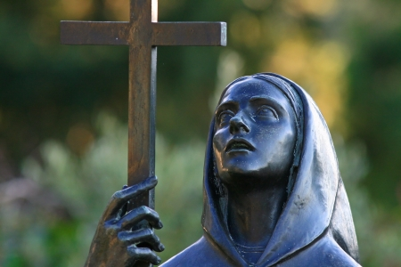 death metal: Statue of a sorrowful woman bearing a cross in a cemetery Stock Photo