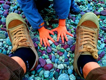 men s feet: Father  's shoes beside Son ' s hands on a colorful rocky beach at the Sea