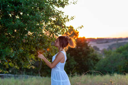 Profile of a young girl in white dress at sunset with blond tied hair near the magic tree