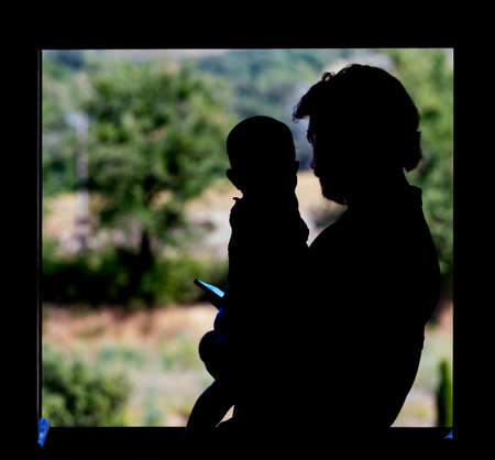 Father looking at smartphone while holding his little child in his arms at the window in silhouette