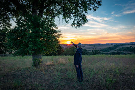 Senior botanist talking with the magic tree at sunset