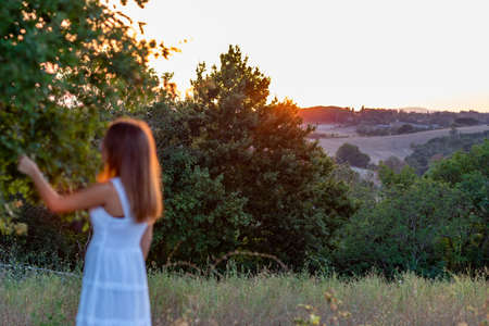 Blurred sunset profile of a young girl with long blonde hair dressed in white as she touches the leaves of the magic tree Stock Photo