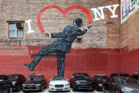 A parking in W17th Street, NYC, with a street wall painting showing a gentleman in pinstripe suit and bowler hat that draws with the spray the heart of I Love NY