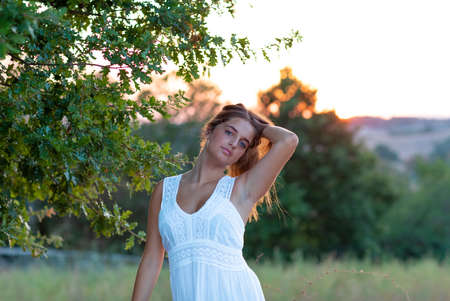 Young girl with blond long hair dressed in white posing at sunset near the magic tree