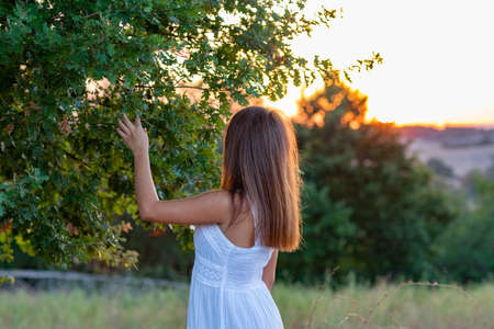 Profile of a young girl with long blond hair dressed in white with her head turned towards the sunset as she touches the leaves of the magic tree Stock Photo