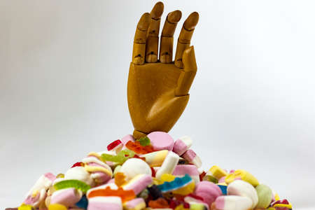 Save me from sugars: a wooden hand sticking out of a mountain of candies Stock Photo