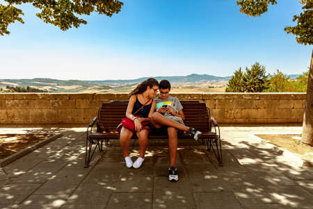 Girl and Boy looking at the cellular on a park bench in San Casciano dei Bagni, Siena