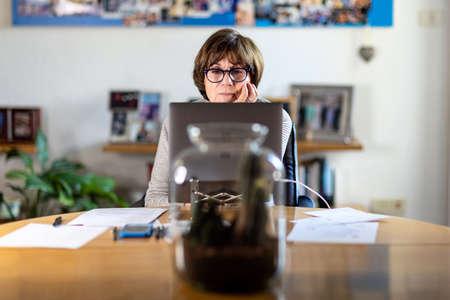 Elderly Teacher or Consultant online working with her laptop