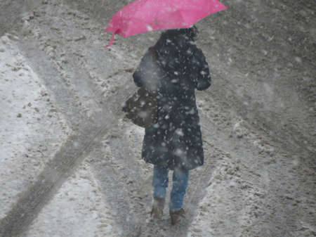 Woman sheltering with an umbrella walks under a snow storm in Rome, Italy