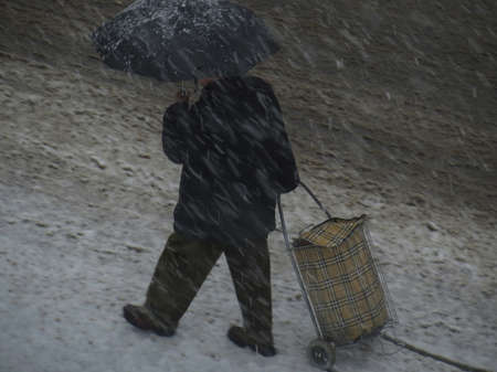 Man sheltering with an umbrella walks under a snow storm in Rome, Italy, pulling a shopping trolley