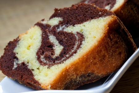 Slices of homemade marble cake on a white plate with brown backround