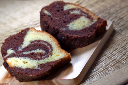 Slices of homemade marble cake on a wooden plate with brown backround photo