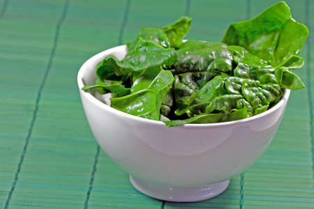 raw spinach leaves in a white bowl with green  background photo