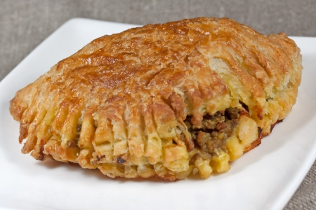 pasty: pasty filled with minced meat on a white plate with beige background