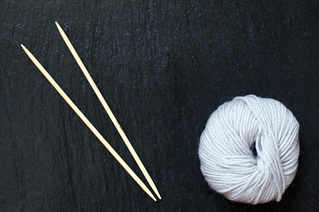 skein of white yarn with bamboo knitting needles with black slate background