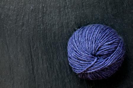 skein of yarn purple with black slate background