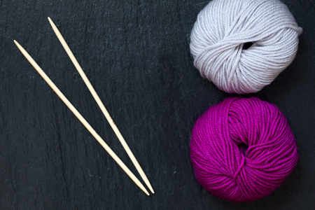 skein of pink and gray yarn with bamboo knitting needles with black slate background Standard-Bild
