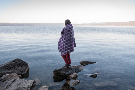 Girl with plaid stands on the stone at lakes coast