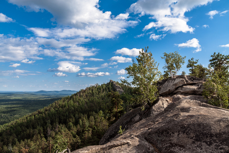 Rocky crest, small birches, shadows on a forest, white clouds and far horizon