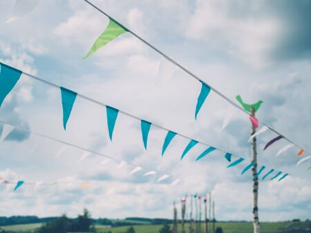 Triangular flags on the rope against clouds during summer festival