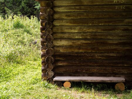 Wall of old rustic log house and wooden bench in the middle of a green meadow
