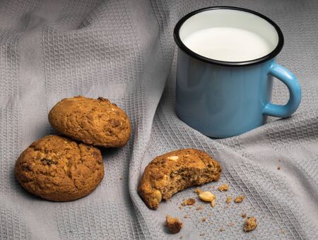Still life with mug of milk and oat cookies on grey textile background