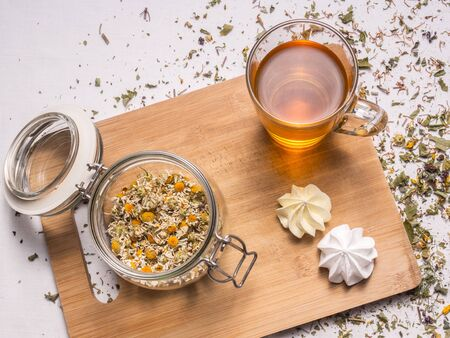 Composition with dried chamomile, glass mug with hot tea, meringues, bamboo board and dried herbal leaves and petals